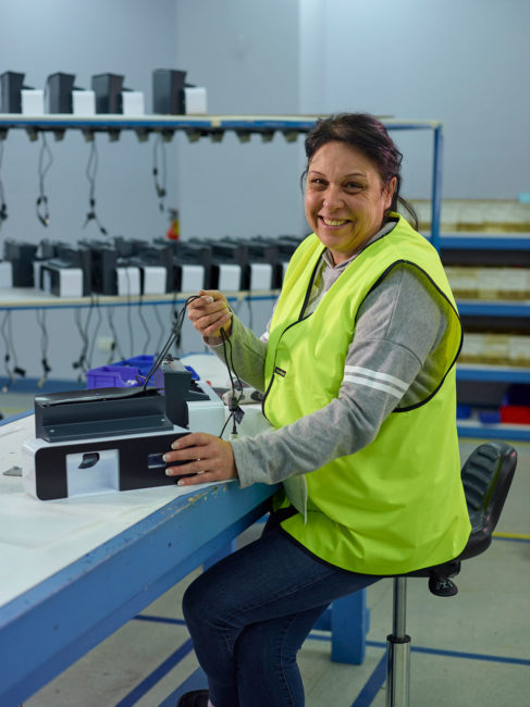 Woman wearing a high-visibility vest working with an electrical device