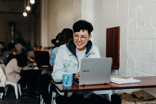 Young woman with short hair and glasses sitting in cafe working on a laptop